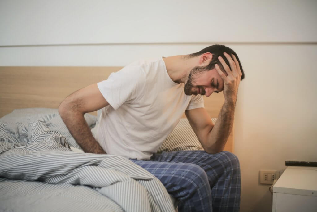young man in sleepwear suffering from headache in morning 3771115 1024x683